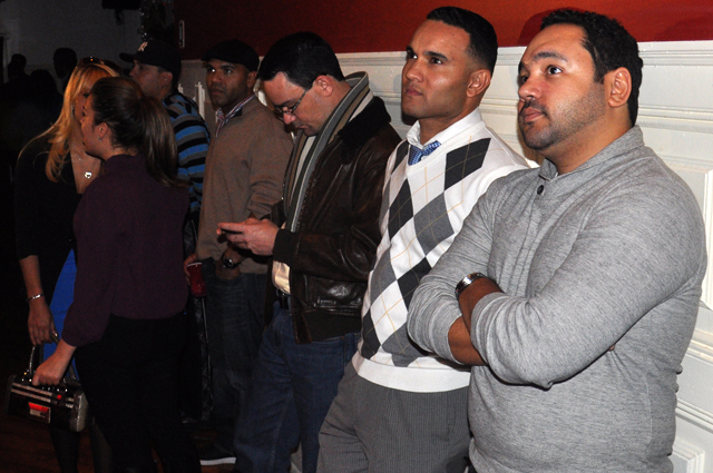 Carlos Sierra (center) and other attendees look on for election results.