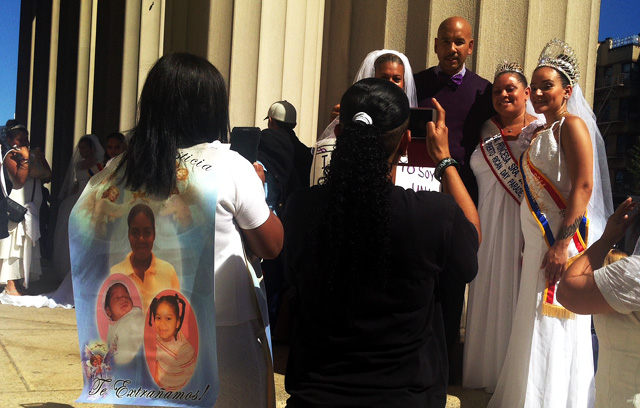 One mother of domestic violence victims wears a banner of her daughter and her granddaughters in honor of their memory.